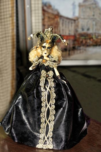 Doll of young Halloween witch in a black evening dress with dark make-up on her face and a spreading hat with a cocked hat on her head.