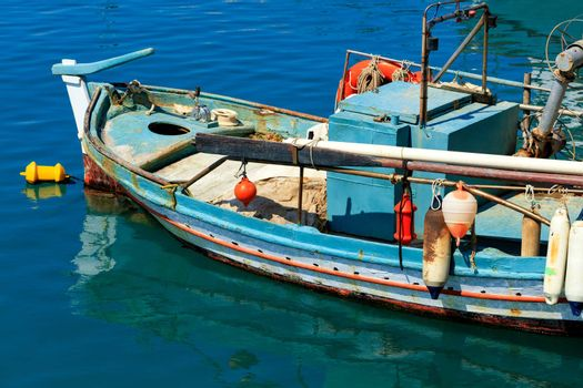 An old wooden fishing boat with raised oars and bright plastic buoys is anchored against the blue water of the Ionian Sea, image with copy space.