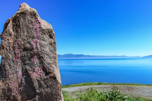 Stone engraved signage at Sayram Lake in Xinjiang, China. (English translation - Sailimu Lake or Sayram Lake)