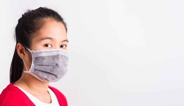 Asian adult woman wearing red shirt and face mask protective against coronavirus or COVID-19 virus or filter dust pm2.5 and air pollution she looking camera, studio shot isolated white background