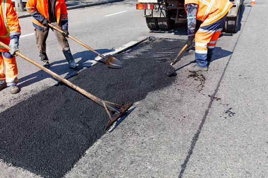 A working group of road workers accurately levels fresh asphalt on a part of the road for repair in road construction, image with copy space.