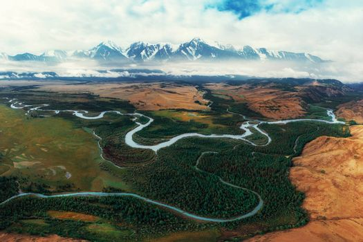 Kurai steppe and Chuya river on North-Chui ridge background. Altai mountains, Russia. Aerial drone panoramic picture.