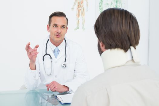 Friendly male doctor in communication with patient at desk in medical office