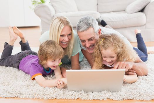 Happy family using laptop together while lying on rug at home