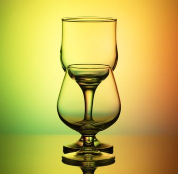 glasses for wine and cognac with a thin contour stand arches after the other, on a bright yellow-green background