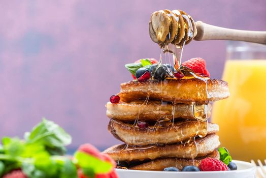 Pouring Honey on Pancakes Stack Topped with fresh Fruits. Shrove Tuesday Breakfast.