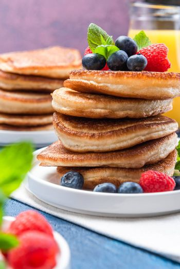 American Pancakes Served with Fresh Berry Fruits and Honey. Shrove Tuesday.