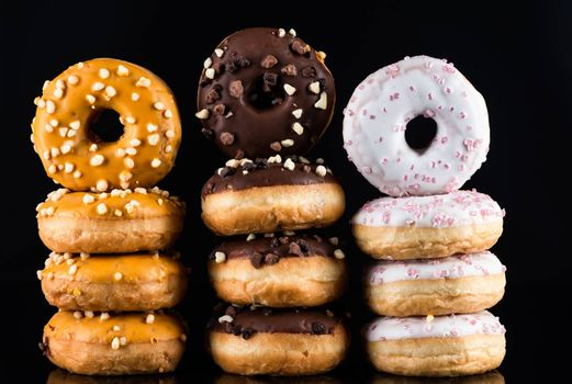 Donuts or Doughnuts Tower on Dark Background. Donut Stack Pile Food Background.