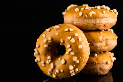 Stack of  Salted Caramel Donuts or Doughnuts on Black Background with Copy Space.