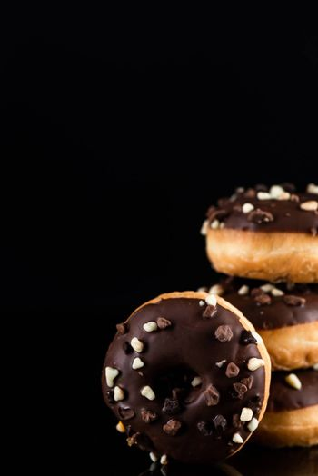 Stack of Chocolate Donuts or Doughnuts on Black Background with Copy Space.