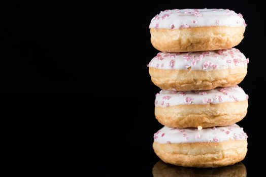 White Chocolate Donuts or Doughnuts Tower on Dark Background .