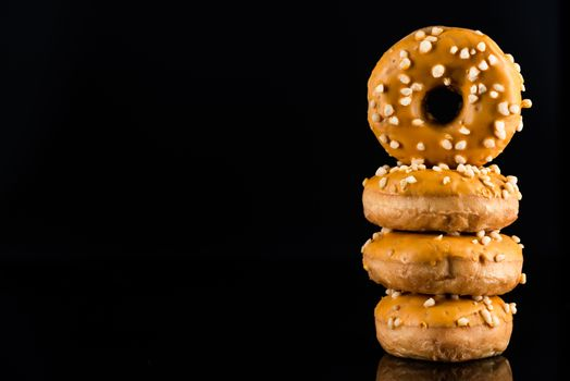 Salted Caramel Donuts or Doughnuts Tower on Dark Background. Copy Space for Text.