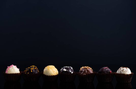 Chocolate Pralines on Dark Background. Copy Space for Text. Close Up Detail View.