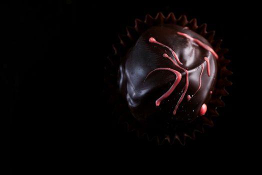 One Single Handmade Chocolate Praline Close Up View. Dark Background with Copy Space.