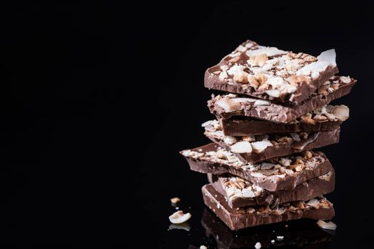 Stack of Broken Chocolate Pieces on Black Background. Copy Space. Closeup View.