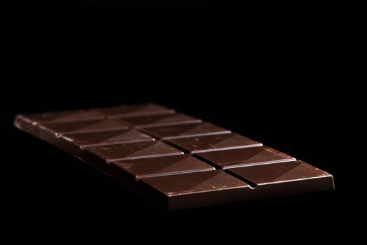 Chocolate Whole Bar on Black Background. Closeup View.