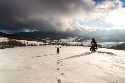 Active Man Standing at Snowy Mountain at Sunrise in Bieszczady, Poland.