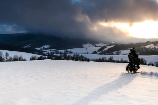 Snowy Meadow at Sunrise. Dramatic Stromy Clouds over Polonina in Bieszczady, Poland.