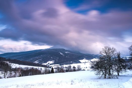 Sunrise in Bieszczady Mountains in Winter. Long Exposure. Snowy Hills and Meadows.