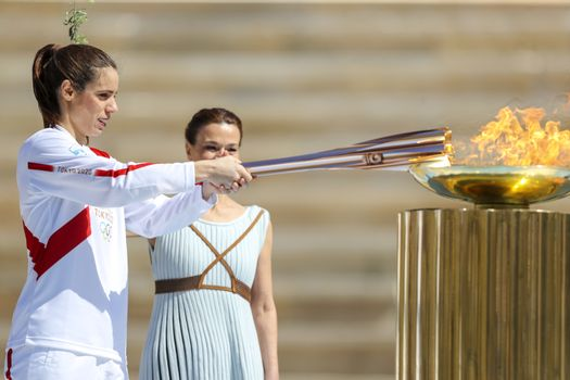 Athens, Greece - March 19, 2020: Olympic Flame handover ceremony for the Tokyo 2020 Summer Olympic Games at the Panathenaic  Stadium. Greek athlet K. Stefanidi (L) is seen lighting the cauldron