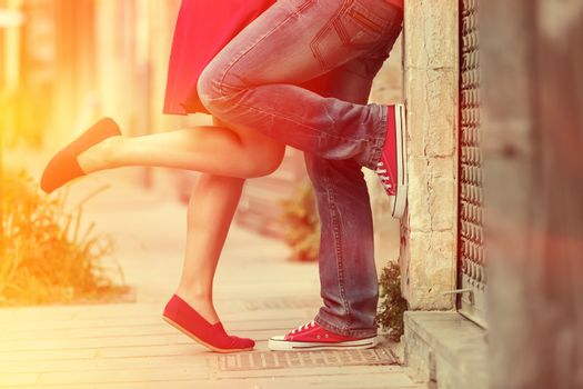 Young couple kissing outdoor. Male and female legs. Cross proces