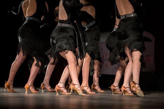 Legs of young dancers on the dance floor
