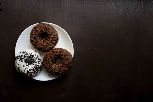 Three doughnuts on a white plate on a brown background