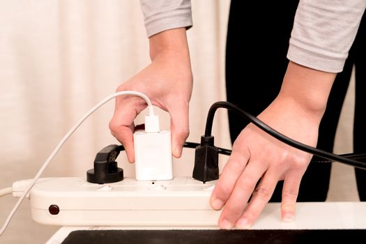 women hand putting the electric plug on the electricity supply c