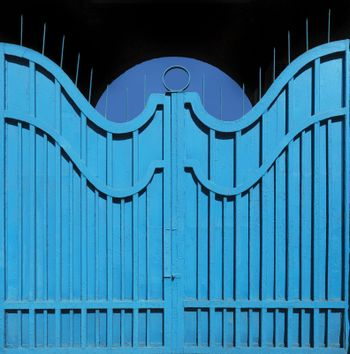 Old metal gate-fence with original structure painted in bright blue paint on the background of the archway