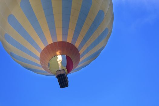 Flight of a balloon in the blue sky, view of the basket overhead