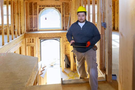 Building inspector looking at new home on holding tablet with hard hat