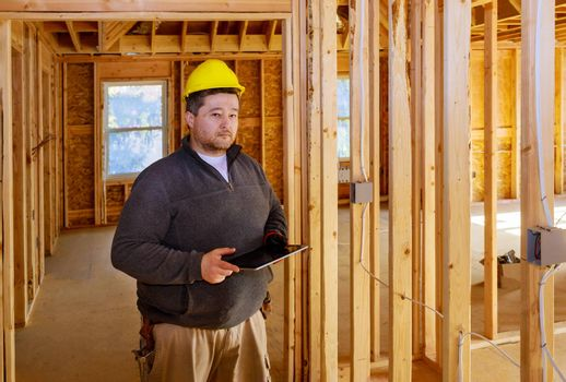 Inspector checking building during house construction in the tablet PC with hard hat