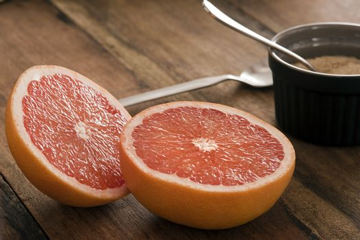 Halved fresh pink grapefruit with a bowl of sugar