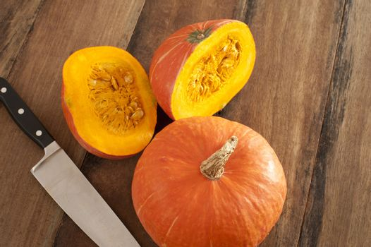 Small whole and halved fall pumpkin or squash