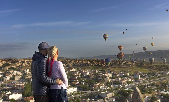 Young people watch dozens of balloons flying over the valleys of Cappadocia at dawn in central Turkey.