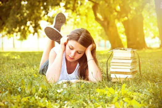 Young beautiful college student girl lying down on the green grass and reading a book at campus at warm day. Education. Back to school conceptual image.