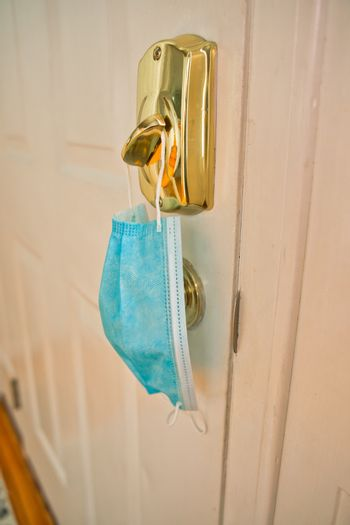Blue mask hanging from lock as a reminder to wear facemask when leaving home to protect face, nose, and mouth from coronavirus