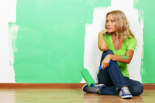 Young attractive woman with paint brush near fresh painted wall finishing renovation copy space for text