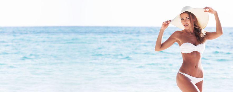 Smiling beautiful woman in white bikini and sun hat at sea beach