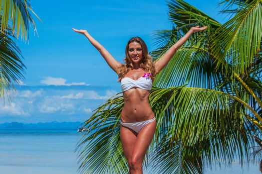 Portrait of young model woman in bikini raising her arms at tropical beach with palms in Thailand
