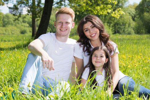 Family of three sitting on spring park meadow grass being happy