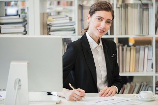 Young female business woman sitting at her workplace with computer monitor and working with financial reports