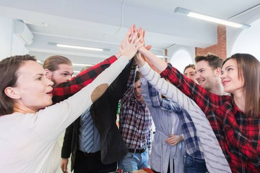 Business people in casual clothes giving high five in the office