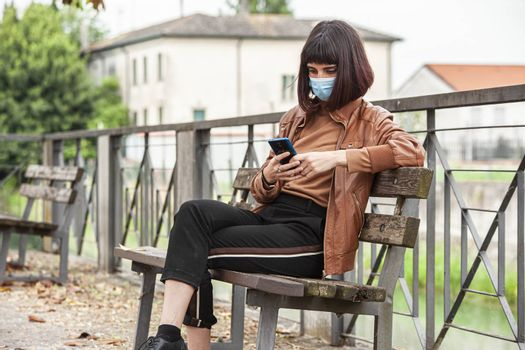 Portrait of a Girl with medical mask at park with smartphone during covid quarantine in Italy