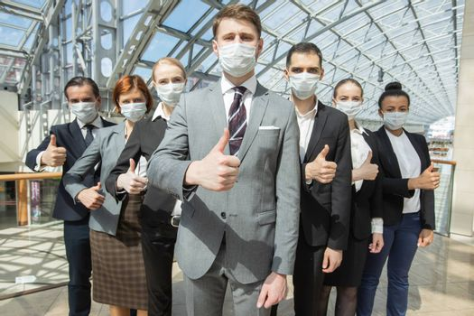 Successful business people with thumbs up wearing surgical masks and standing together, healthcare and covid-19 prevention concept