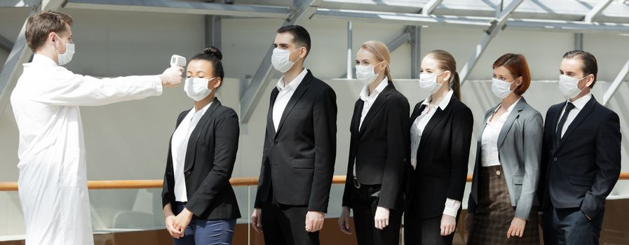 Doctor wearing protective surgical mask using infrared forehead thermometer (thermometer gun) to check body temperature for virus symptoms of business team waiting in a line