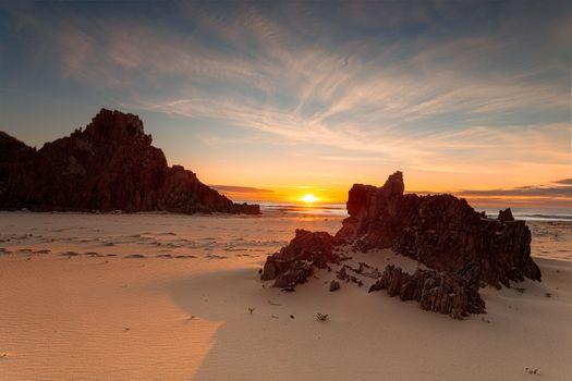 Golden sunrise warm sunlight on the remote rocky beach