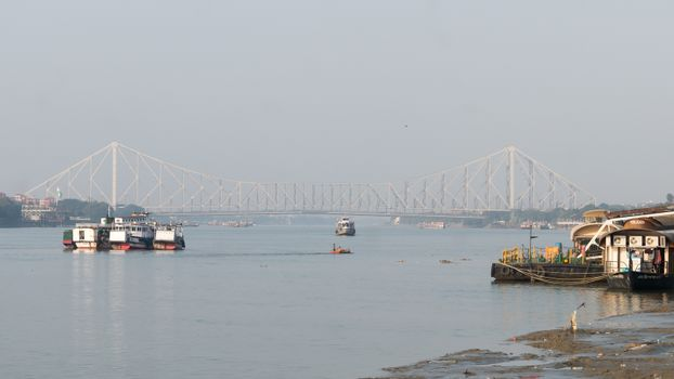 Panoramic Scenics Howrah bridge over Hooghly river. Photography in winter sunset from Babu Ghat Calcutta Riverside Area Kolkata, West Bengal, India, South Asia Pac January 2020