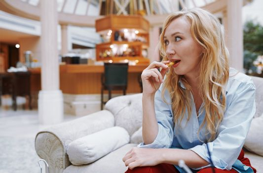 Woman enjoying snack and sitting at the hotel lobby