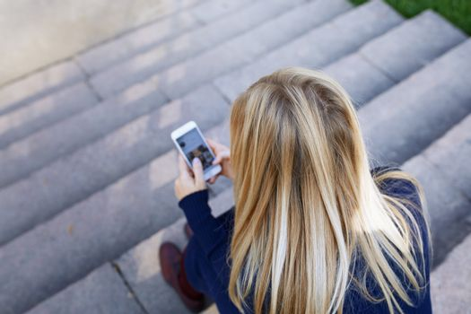 Business woman sitting on city stair steps and holding smartphone